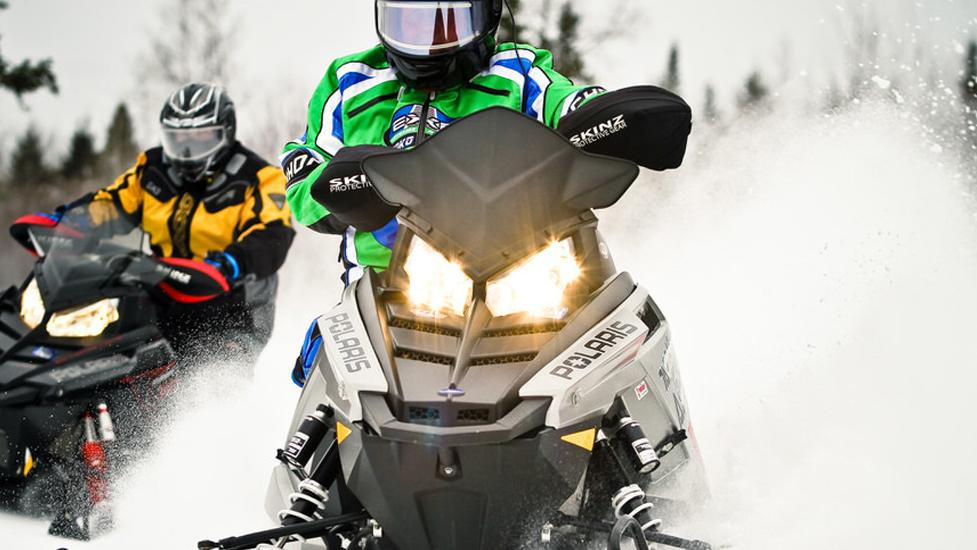 2 people riding their snowmobile, as it kicks the snow behind them