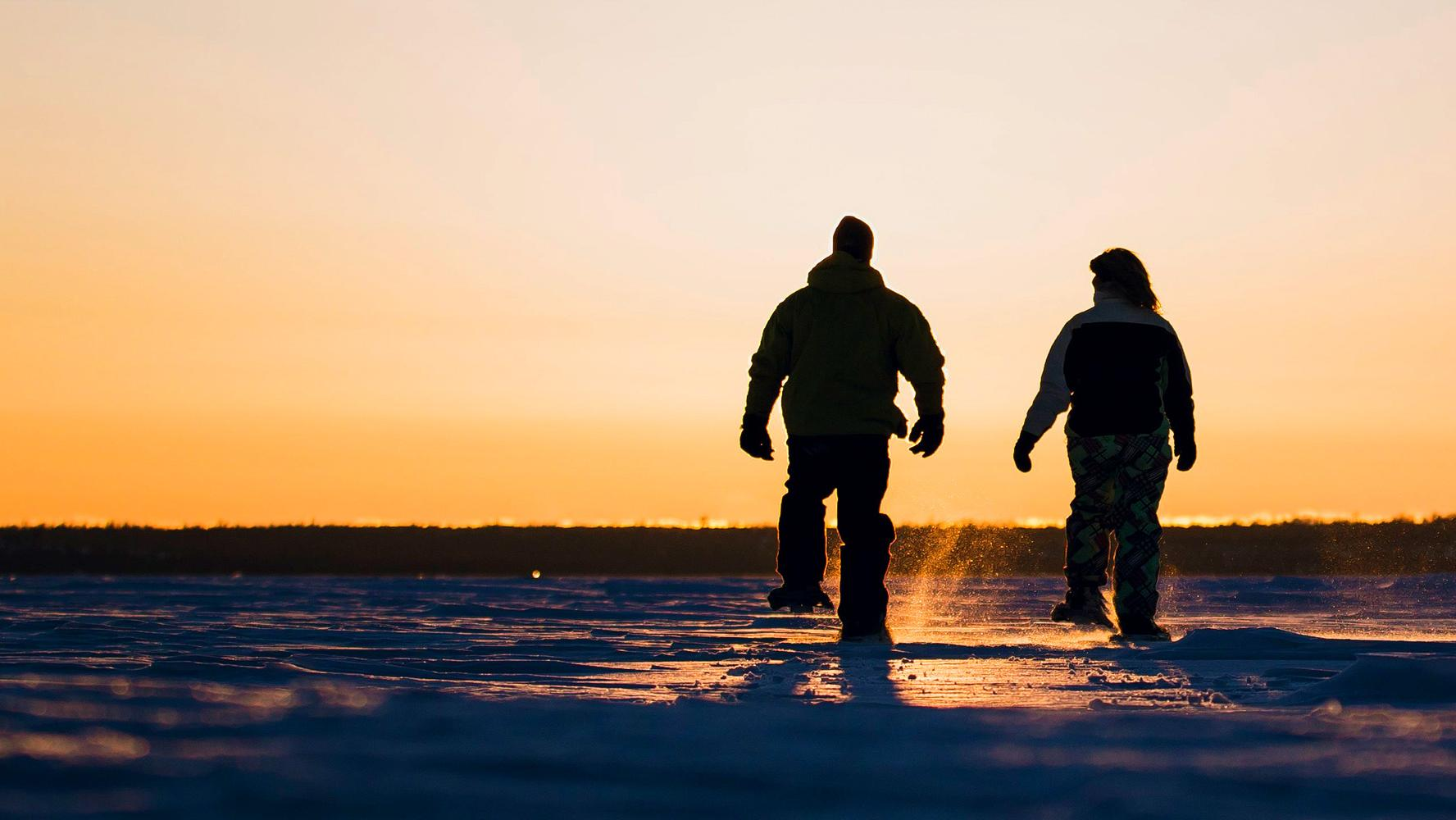 Two people snowshoeing as the sun goes down