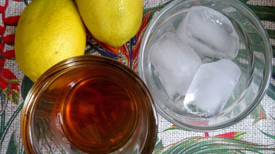 A glass of whisky and glass of ice sit beside two lemons on a table