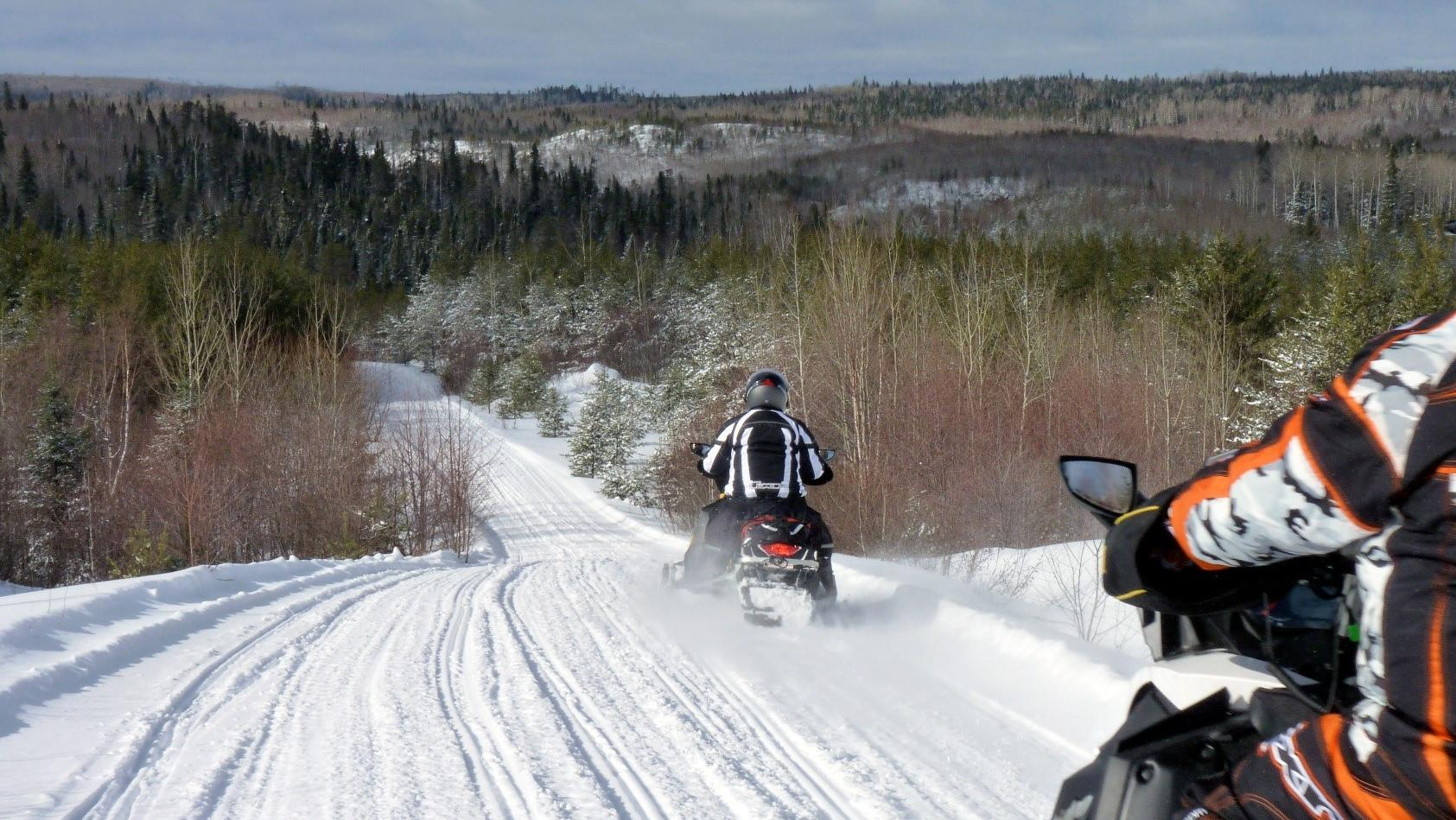 Two snowmobilers on a wide open trail on a bright sunny day