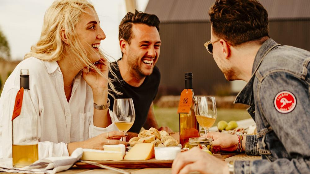 A group of friends gather at a picnic table to enjoy food and wine