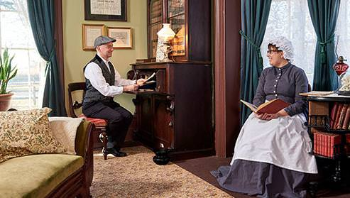 Inside the Bell Homestead, a man and woman dressed in clothes from 1874 smile at each other while sitting in chairs and reading