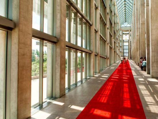 Visitors explore a long, sunlitglass-pannelled hallway.