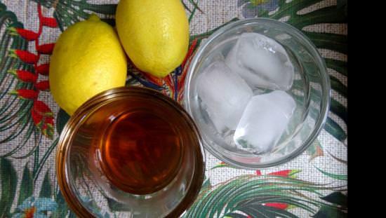 Un verre de whisky et un verre de glaçons sont posés à côté de deux citrons sur une table.