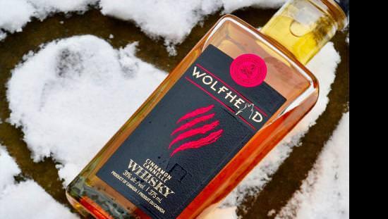 Une bouteille de whisky à la cannelle Wolfhead refroidit sur un cœur formé dans la neige au sol.