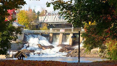 Bracebridge Falls, vue de l'autre côté de la rivière et au pied des chutes. Il y a des feuilles mortes aux couleurs vives sur le sol, et au-dessus des chutes se trouve le Silver Bridge.