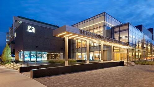 Entrée principale du Burlington Performing Arts Centre, grand bâtiment de plusieurs fenêtres allant du sol au plafond, avec des murs en pierres.