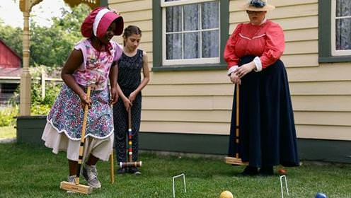 One woman and two young girls dressed in pioneer clothing play croquet next to historic house.