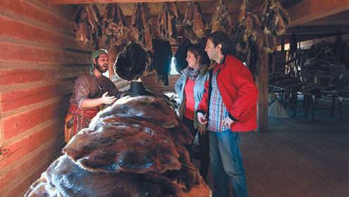 A fur trader displays his wares to a couple of visitors at a trading post