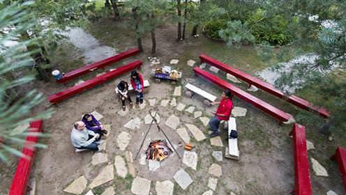 Des visiteurs écoutent un guide, assis sur des bancs autour d'un feu dans la forêt