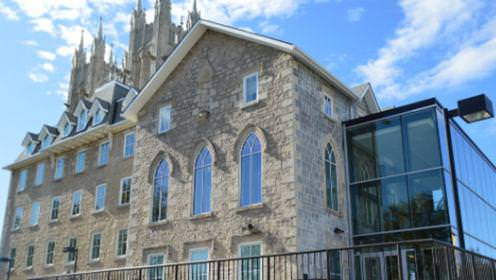 A large renovated stone convent with a large glass extension on the front of the building.