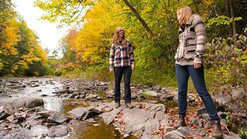 A couple shares a laugh along a stream in the autumn