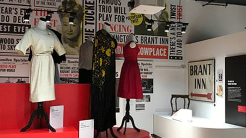 Exposition de vêtements d'intérieur au Joseph Brant Museum. La salle est pleine de mannequins vêtus de  robes différentes. Des photos de femmes s'alignent sur le mur du fond, avec des citations et des titres de l'exposition.