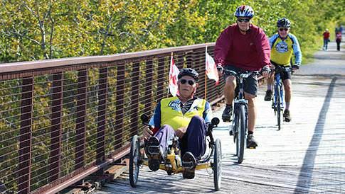 Des cyclistes traversent un pont du sentier transcanadien par une journée ensoleillée.Des piétons marchent dans le sentier de gravier en arrière-plan, qui est entouré d'une végétation luxuriante.