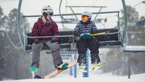 A snowboarder and skiier share a chairlift to the top of the mountain