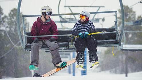 Un planchiste et un skieur partagent un télésiège vers le sommet de la montagne