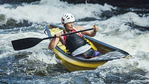 A solo canoeist navigates whitewater rapids