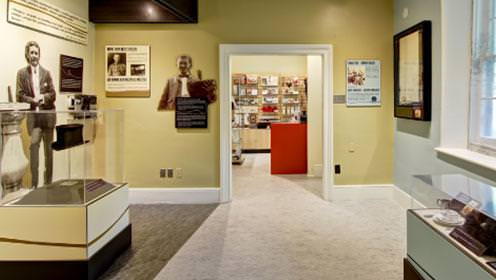 An indoor exhibit at the McCrae House with glass display cabinets and pictures and plaques on the walls.