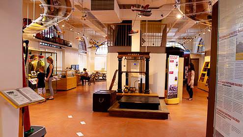 Vue de l'intérieure du North Bay Museum, avec des fiches informatives le long des murs, un présentoir à gauche et des escaliers au milieu d'une pièce. Des modèles d'avions sont suspendus au plafond.