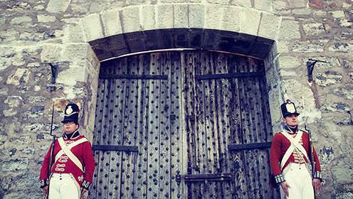 Deux soldats vêtus d'uniformes de la guerre de 1812 se tiennent de chaque côté d'une grande porte en bois menant à un grand fort en pierres.