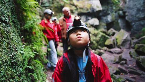 Child with hard hat and head lamp looking up in cave