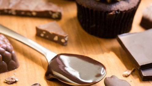 A close up of metal spoon covered in chocolate, surrounded by a chocolate cupcake and chocolate bark.