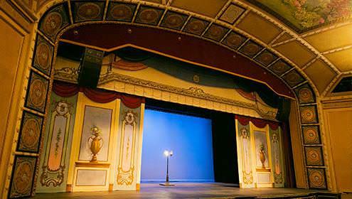 Petit théâtre intérieur avec scène entourée de carreaux ornementés et de peintures. Une lampe torchère est posée au centre de la scène.