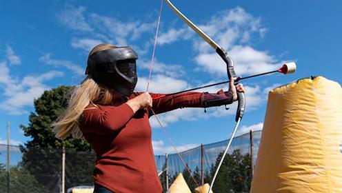 Une femme aux longs cheveux blonds et au masque facial noir pointe un arc et une flèche vers une zone entourée d'un filet noir. La zone contient des petites cibles jaunes gonflables.