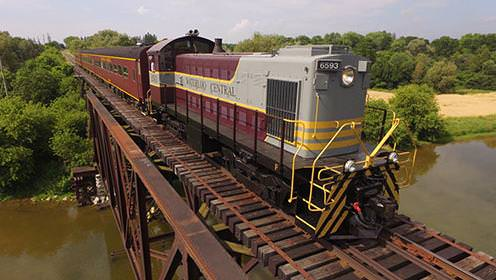 A large heritage train crosses a train bridge over a wide river.
