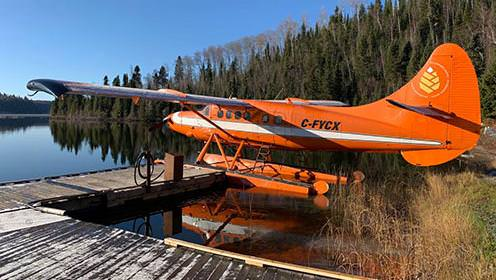 An orange seaplane tied to the dock on the shores of a lake.