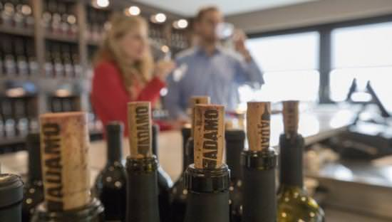 Corks on wine bottles, while a man and woman enjoy wine in the background