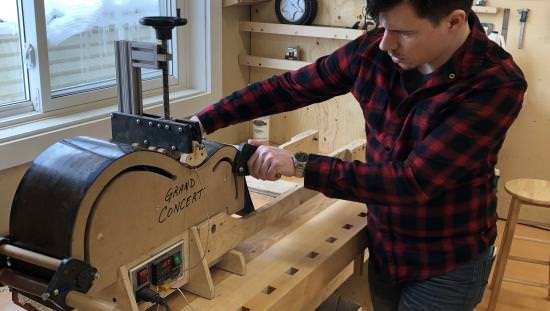 A man handcrafting an acoustic guitar