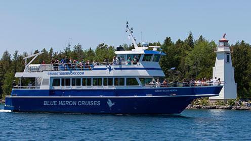 """Sur un grand bateau, des gens ayant pris place à l'avant et sur le pont supérieur naviguent près d'un phare.  Sur la coque du bateau, on peut lire """"Blue Heron Cruises""""."""