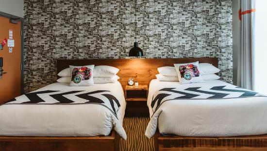 La literie et l'éclairage doux mettent en valeur le mur d'accent dans une chambre d'hôtel de charme