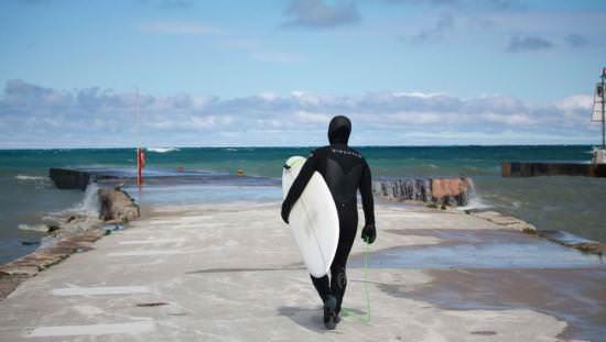 Surfer holding surf board walking towards a lake