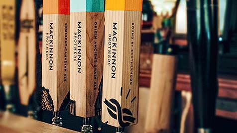 Trois fûts de bière en bois, étiquetés en rouge, bleu ou jaune selon les différentes variétés de bière Mackinnon Brothers : Crosscut Canadian Ale, Origin Ancient Grain Ale et Bound By Brotherhood.