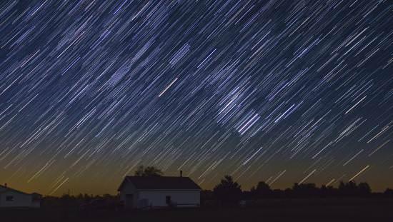 Un spectacle dramatique d'étoiles illumine le ciel sombre sur une scène de ferme rurale