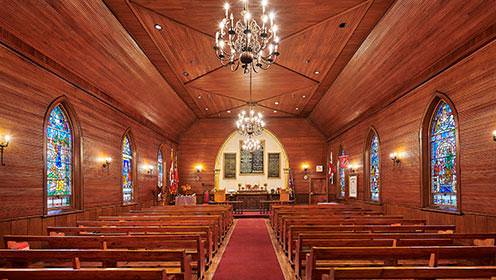 The inside of a chapel covered with wooden panelling and three stained glass windows on each side. An aisle separates two rows of wooden pews and three chandeliers are hanging above.