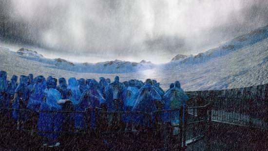 Une foule de gens en manteaux de pluie devant un écran de cinéma
