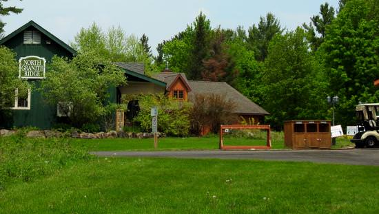 Manicured green lawns and forest surround the main golf lodge