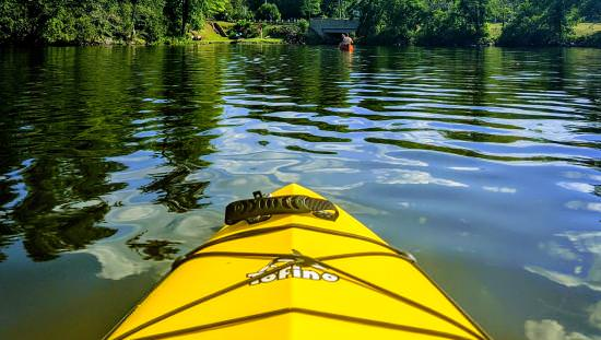 The front of a yellow kayak paddling in a picturesque lake
