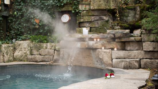 Hotspring pool surrounded by flagstone walkway and sending up a soft spray