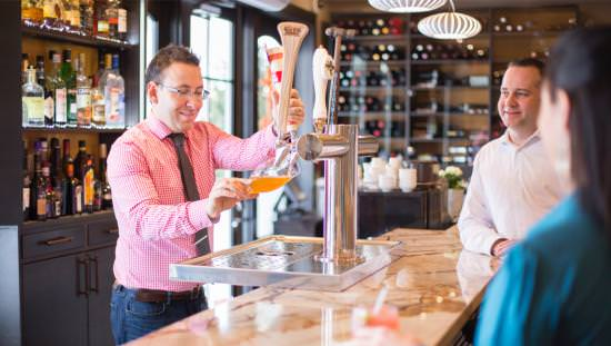 Bartender in modern bar pouring drink for smiling customers
