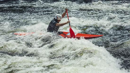 Kayakiste solo pagayant sur des rapides d'eau vive