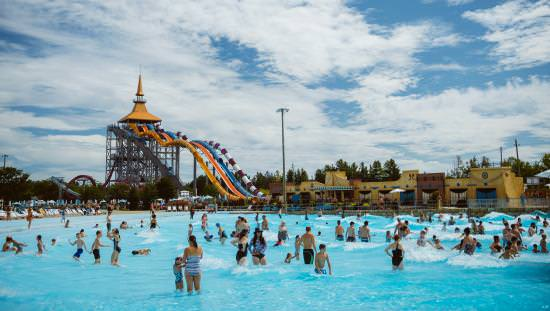 Large swimming pool filled with adults and children with water-slides on far side