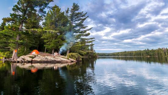 A couple sitting between a tent and a campfire on a rocky, lakeside outcrop