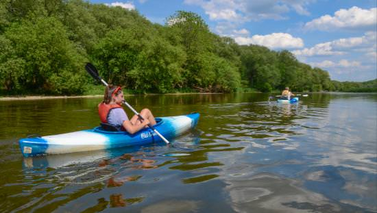 Woman paddling kayak down treelined river following second kayak