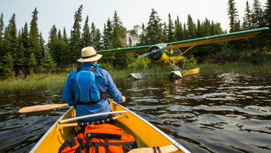 Person in a yellow canoe on a lake with a float plane and forest in the foreground