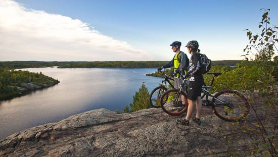 A couple standing next to their mountain bikes on a rocky hilltop overlooking a lake