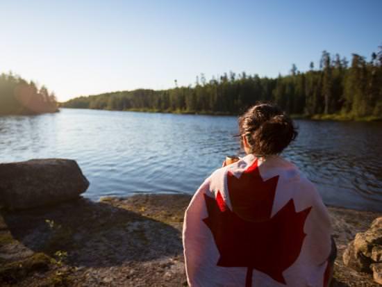 Une fille enveloppée dans une serviette avec le drapeau canadien s'assied pour admirer un beau lac